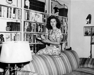 Black & white photo: Shirley Temple sitting on sofa with book